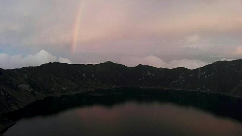 Coucher de soleil rosé sur le cratère et arc-en-ciel en fond
